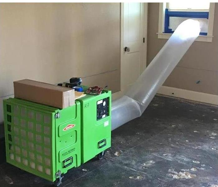 green air scrubbers with a flex duct channeling air our of a room via a window