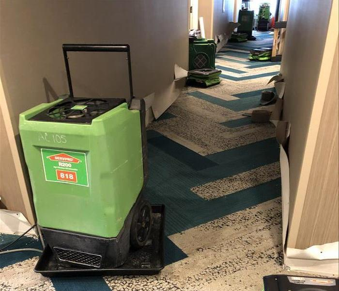 SERVPRO equipment cleaning up mold and water in a hotel corridor