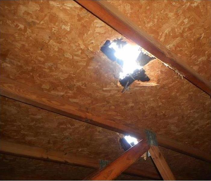 A ceiling with a huge hole in it after a storm